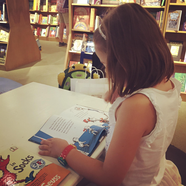 Mädchen liest ein Buch im Buchladen